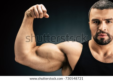 selective focus of strong man showing muscles isolated on black #730548721