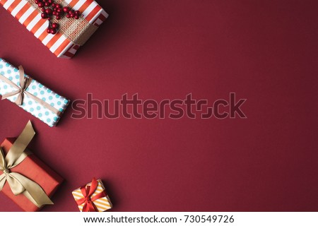 top view of arranged wrapped christmas gift boxes with ribbons on red tabletop #730549726