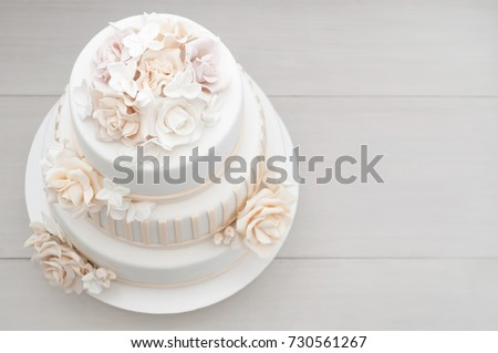 Three-tiered white wedding cake decorated with flowers from mastic on a white wooden table. Picture for a menu or a confectionery catalog. Top view.