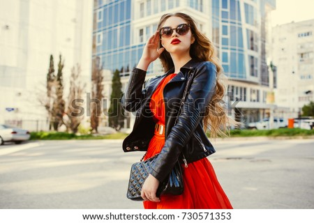 Fashion outdoor portrait of gorgeous long hair woman in elegant red dress and black leather jacket - autumn style. Fashionable hipster girl in trendy clothes posing at city street lifestyle portrait. #730571353