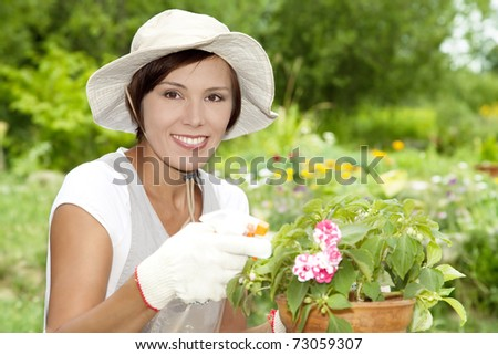 Young woman watering flowers in a garden #73059307