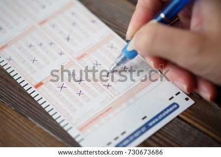 Photo on top of person marking in lottery ticket #730673686