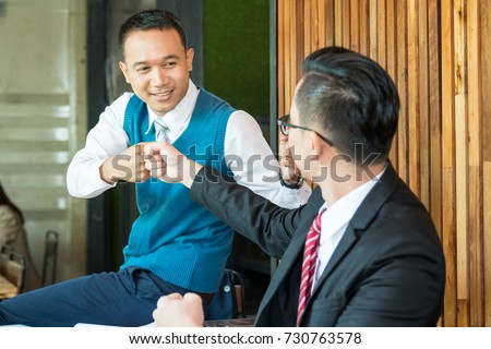 Businessman in a coffee shop. Two modern businessman fist bump after a good deal.  #730763578