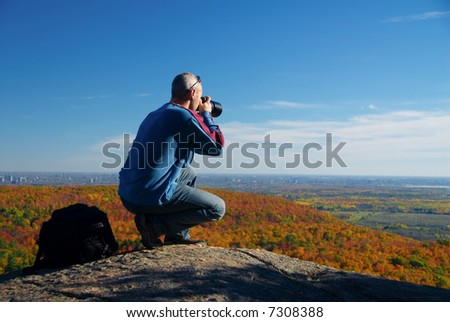 male photographer shooting at the top of a mountain