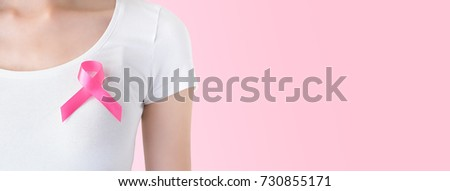 Woman in white t-shirt with satin pink ribbon on her chest, supporting symbol of breast cancer awareness campaign in October - panoramic banner with copy space