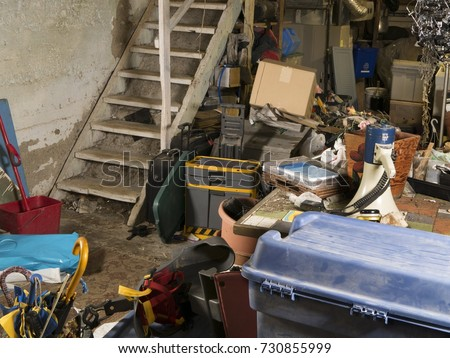Old dingy residential unfinished basement cluttered with storage of random things #730855999