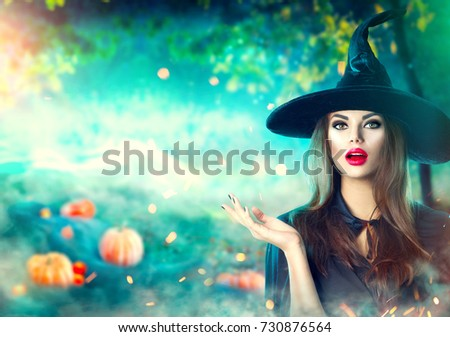 Halloween Witch pointing hand over dark magic field with  Pumpkins and magic lights in forest. Beautiful young surprised woman in witches hat and costume holding pumpkin. Wide Halloween party design #730876564