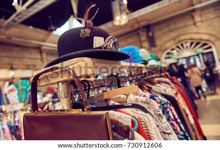 Vintage second hand hat and clothes rail showing colourful vintage clothes on coat hangers. #730912606