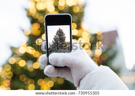 holidays, technology and people concept - hands with smartphone photographing christmas tree