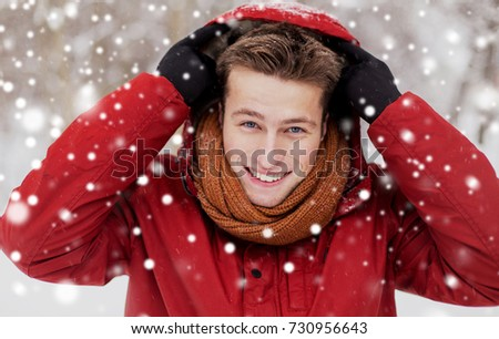 people, christmas, winter and season concept - happy smiling man in jacket and scarf wearing hood outdoors #730956643