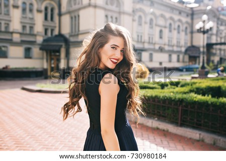 Portrait from back of elegant girl with long curly hair walking on steer on old building background. She has black dress and red lips. She is smiling to camera. #730980184
