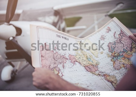 Cropped image of man holding the world map in hands while standing near private plane in airport. Choosing the next destination. #731020855