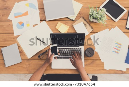 Office workspace top view. African-american businessman working at wooden desk, using laptop and various objects all around #731047654