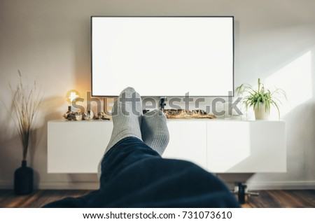 Man Watching TV in his living room, point of view perspective. Royalty-Free Stock Photo #731073610