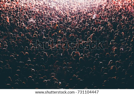 Colorful crowd of people of a big music festival in a stage lights as a beautiful background #731104447