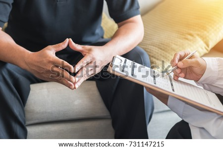 Male patient having consultation with doctor or psychiatrist who working on diagnostic examination on men's health disease or mental illness in medical clinic or hospital mental health service center #731147215