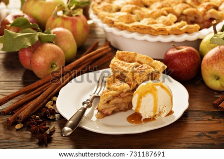 Piece of an apple pie with ice cream scoop and caramel sauce on a plate, fall baking concept #731187691