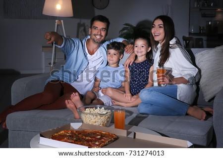 Happy family watching TV on sofa at night Royalty-Free Stock Photo #731274013