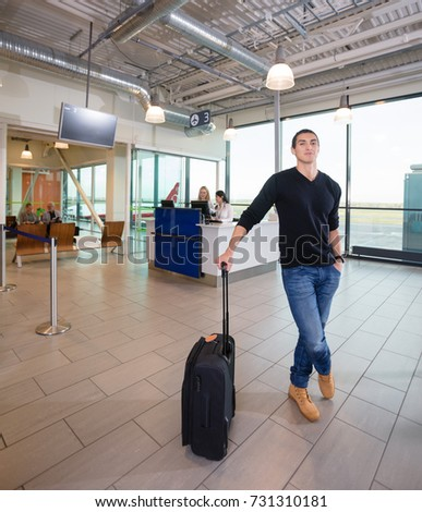 Confident Male Passenger With Luggage At Airport Terminal #731310181