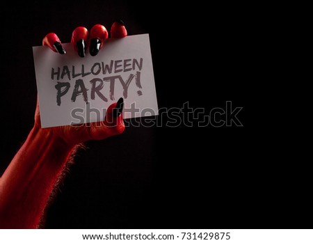 spooky monster hand holding a halloween sign #731429875