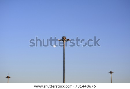 Lighting poles of the airfield against the background of a bright moon #731448676