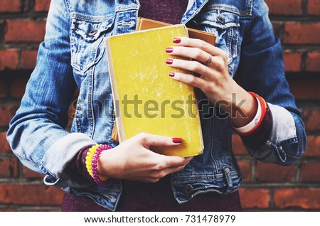 Young student in jeans jacket holding books in her hands Royalty-Free Stock Photo #731478979
