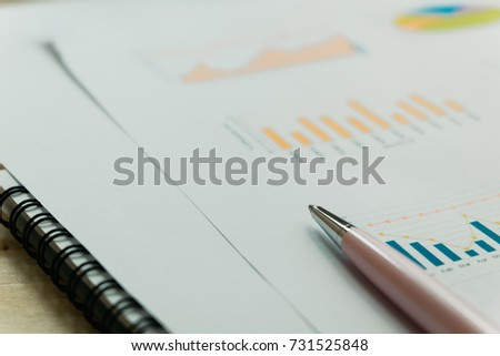 pink pen placed on information paper has bar chart and other data are background. this image for business, education, info, meeting concept #731525848