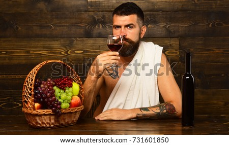Viticulture and autumn harvest concept. Man with beard holds glass of wine on vintage wooden background. God Bacchus with interested face wearing white cloth sits by wine bottle and basket with fruit #731601850