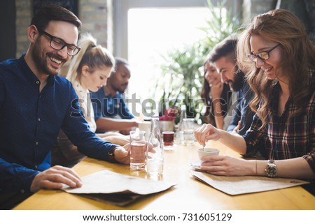 Colleagues from work socializing in restaurant and eating togeth #731605129