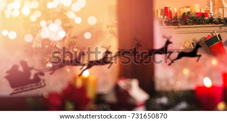 Silhouette of santa claus and reindeer against christmas tree and christmas stocking at home