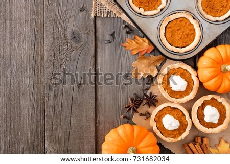 Autumn baking scene side border with pumpkin tarts over a wood background Royalty-Free Stock Photo #731682034