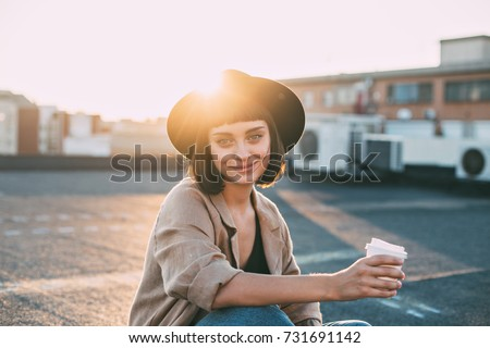 Attractive young millennial student or fashion model in hipster outfit poses for camera on top of rooftop with sun light leaks, smiles and holds coffee cup. #731691142