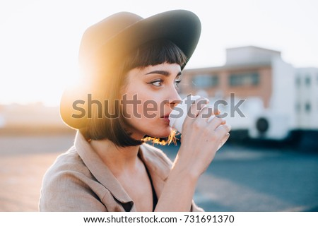 Attractive adorable woman with natural makeup sips on coffee in early morning on sunrise or sunset with light leaks, from to go cup, wears hipster fedora hat #731691370