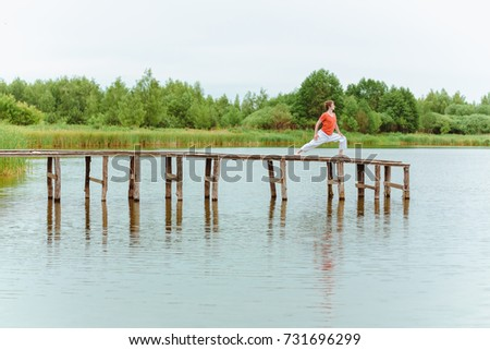 A man doing yoga on wooden pier at the lake #731696299