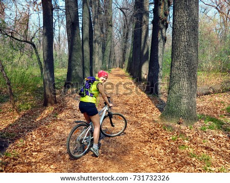 a young woman on a bicycle rides along the avenue with yellowed fall foliage in a grove #731732326