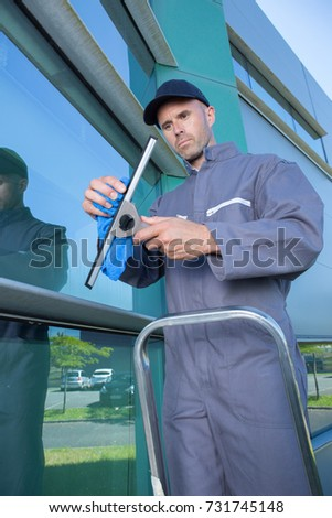 man cleaning windows with squeegee #731745148