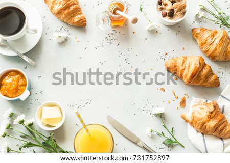 Continental breakfast captured from above (top view, flat lay). Coffee, orange juice, croissants, jam, honey and flowers. Grey stone worktop as background. Layout with free text (copy) space. #731752897