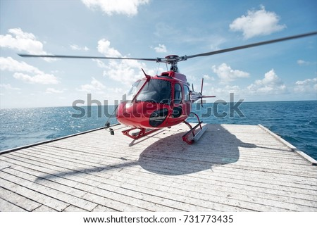 Red Helicopter on a Floating Helipad in the Great Barrier Reef near Cairns, Queensland, Australia #731773435