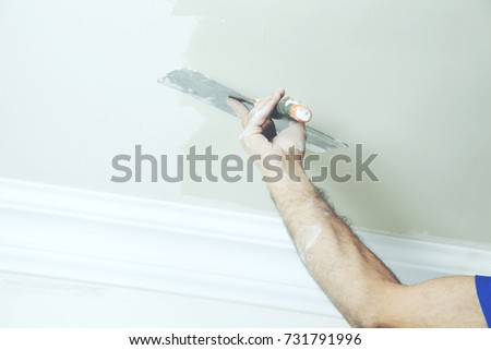 Closeup of repairman hand plastering a wall with putty knife or spatula #731791996