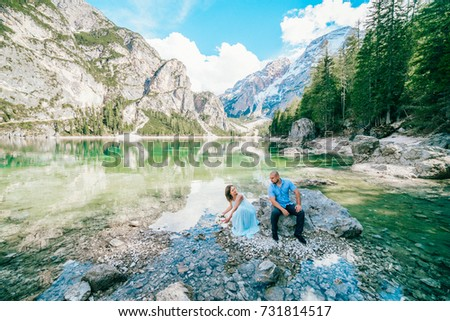 Young couple near lake lago di braies,Dolomite,Italy hold the hand stand at the stone at lake. #731814517