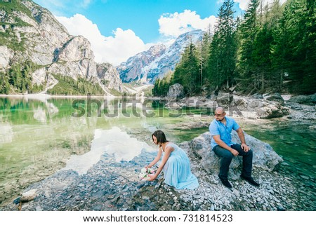 Young couple near lake lago di braies,Dolomite,Italy hold the hand stand at the stone at lake. #731814523