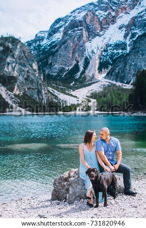 Couple with dog. Beautiful young couple playing with dog while sitting near the lake braies in south tyrol, italy #731820946