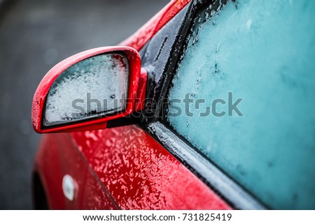 Closeup mirror and a window of a red car in frost Royalty-Free Stock Photo #731825419