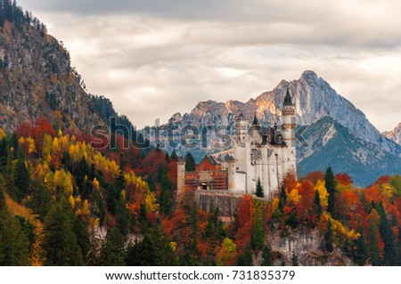 Picturesque sunset view of Neuschwanstein Castle with autumn trees and colorful sky on background, Bavaria, Germany. Beautiful colorful autumn scenery. #731835379