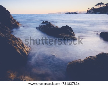 Long exposure shot of the rocks in the sea Royalty-Free Stock Photo #731837836
