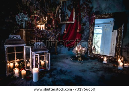 dark decor with dried flowers, vases, chandeliers, textured fabrics against the wall with a golden frame, a wooden table in a luxurious royal Victorian style,burning candles in old lanterns,old mirror