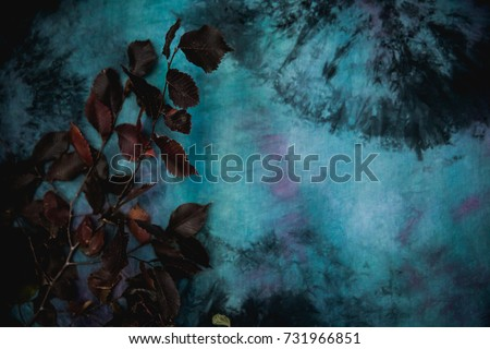 Textured fabric of turquoise color with divorces and burgundy leaves