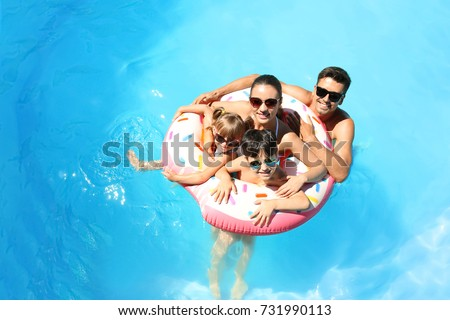 Happy family with inflatable donut in swimming pool Royalty-Free Stock Photo #731990113