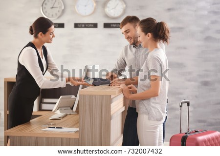 Young couple paying for hotel room at reception Royalty-Free Stock Photo #732007432
