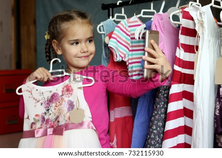 Cute preschooler girl making selfie on mobile phone in chosen new lovely dress in child fashion store; she is happy. Sale, gifts, Christmas, holidays; beauty concept, place for your brand on tag #732115930